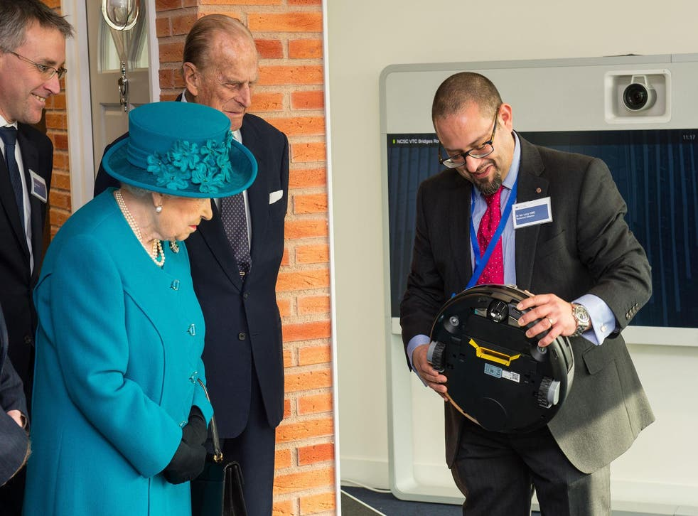 Dr Ian Levy shows the Queen and the Duke of Edinburgh a robot vacuum cleaner which could be vulnerable to cyber attack