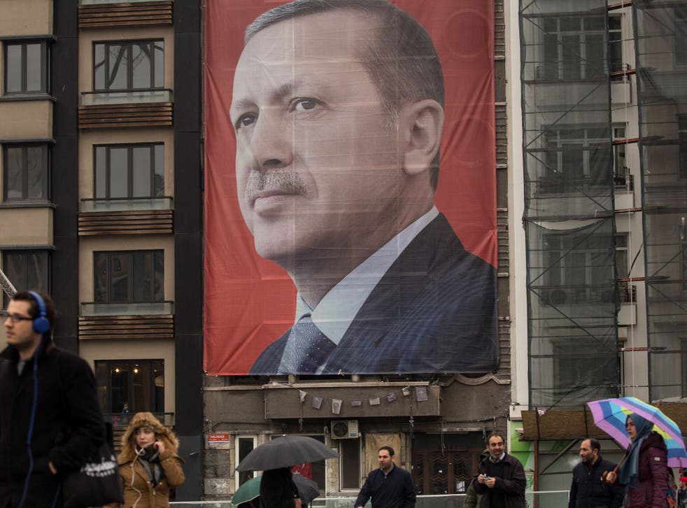 People walk past a large banner showing the portrait of Turkish President Recep Tayyip Erdogan in Taksim Square