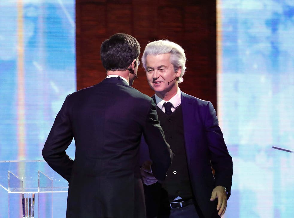 Netherlands' far-right politician Geert Wilders (R) of the PVV party and Netherlands' prime minister Mark Rutte of the VVD Liberal party shake hands before debating on 13 March, 2017