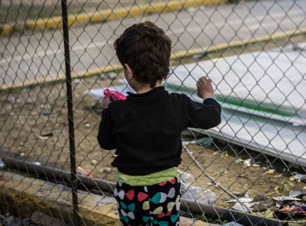 A young girl holds the fence in Kara Tepe camp on the Greek island of Lesbos