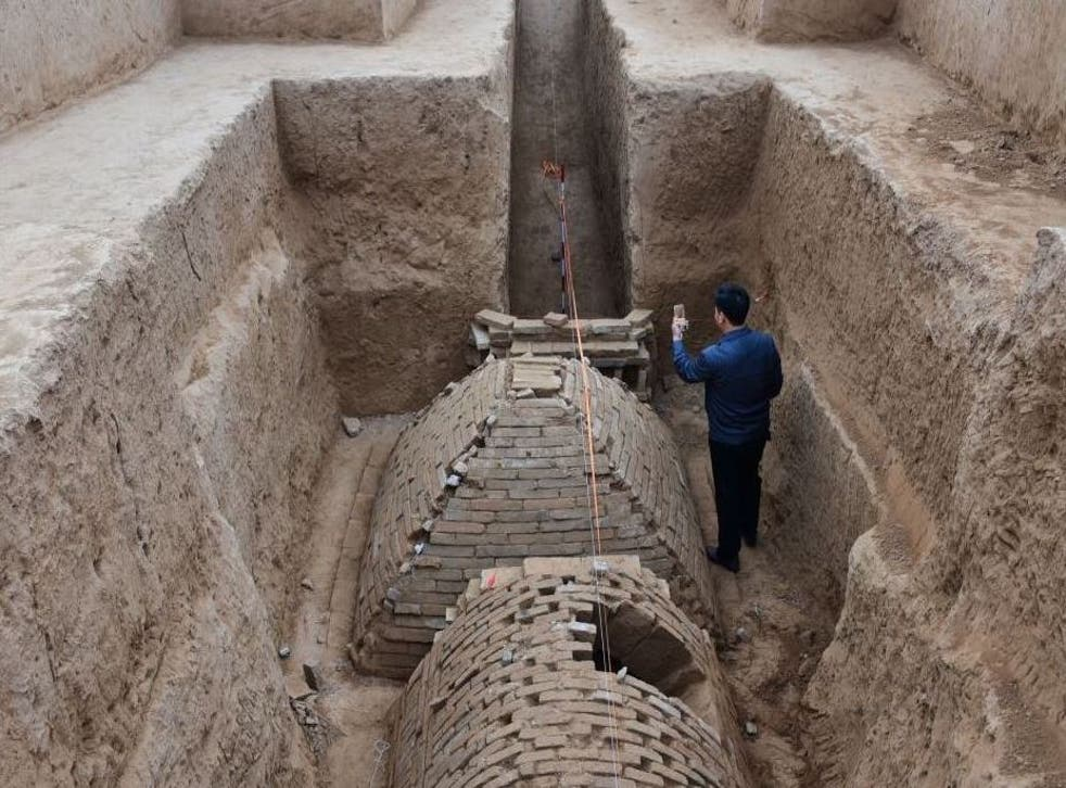 Chinese archaeologist investigates a tomb in the shape of a pyramid