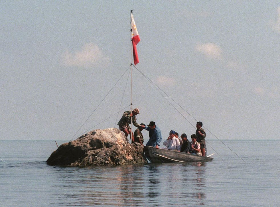 A team of navy personnel and three Philippine congressmen standing on a tiny rock in the Scarborough Shoal with a Filipino flag in protest at Chinese land grabbing
