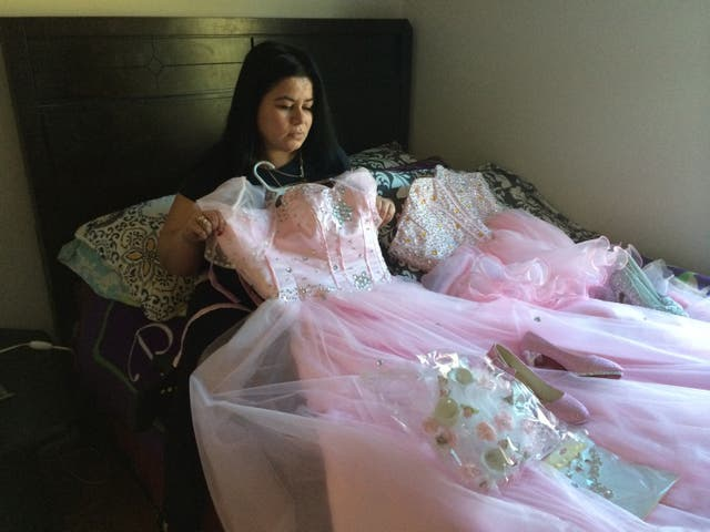 Maria holds the dress her daughter Damaris picked for her quinceañera [15th birthday celebration]