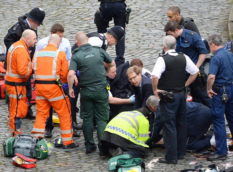 Conservative MP Tobias Ellwood (centre) helps emergency services attend to a police officer outside the Palace of Westminster, London, after a policeman was stabbed and his apparent attacker shot by officers in a major security incident at the Houses of Parliament