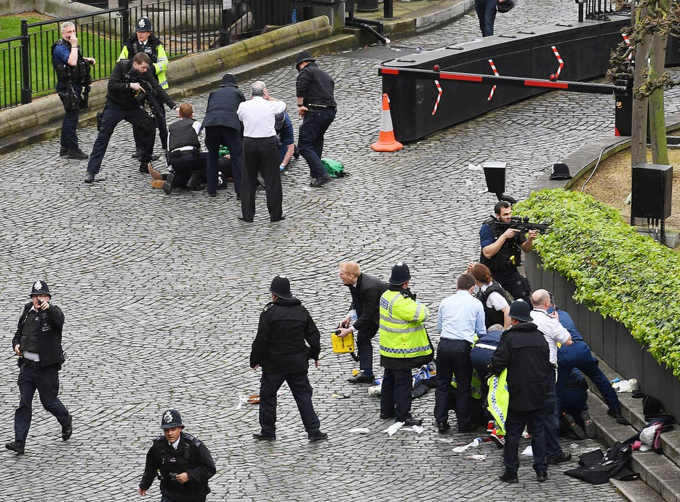 A policeman points a gun at a man on the floor (top) while emergency services attend him and a police officer (bottom) outside the Palace of Westminster, London, after policeman was stabbed and his apparent attacker shot by officers in a major security incident at the Houses of Parliament