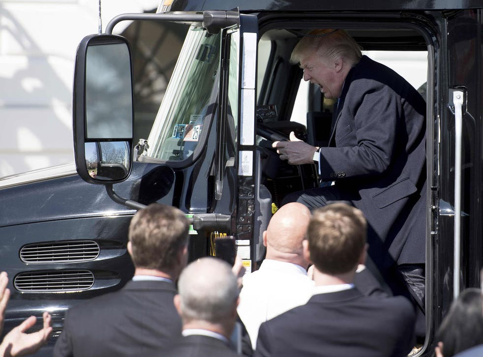 Donald Trump sits in the drivers seat of a semi-truck as he welcomes truckers and CEOs to the White House in Washington, DC, March 23, 2017