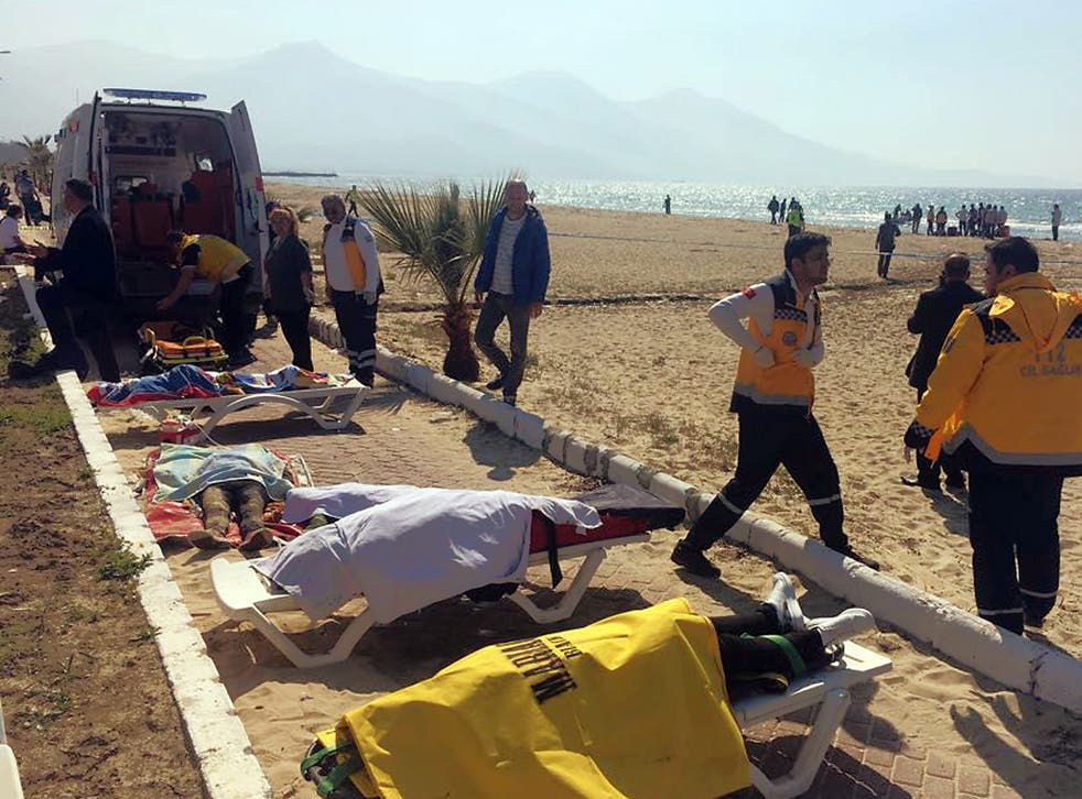 Turkish rescue workers and medics work next to the bodies of migrants laid out near an ambulance in Kusadasi, Turkey