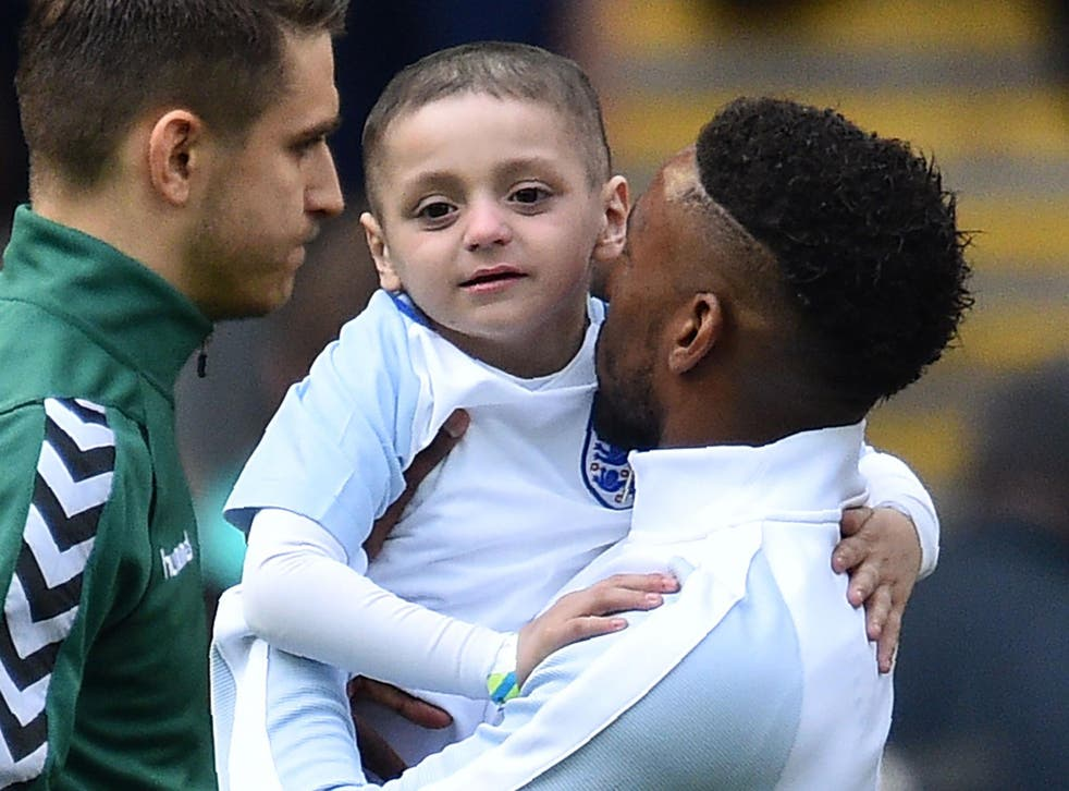 England's striker Jermain Defoe (R) holds Bradley Lowery, a five-year-old suffering from terminal cancer, mascot for the match, ahead of the World Cup 2018 qualification football match between England and Lithuania at Wembley