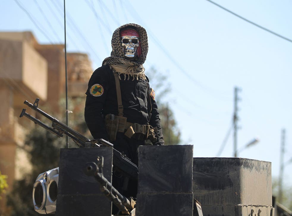 An Iraqi soldier stands guard in Mosul's al-Jadida area, where air strikes have killed a large number of civilians in recent days