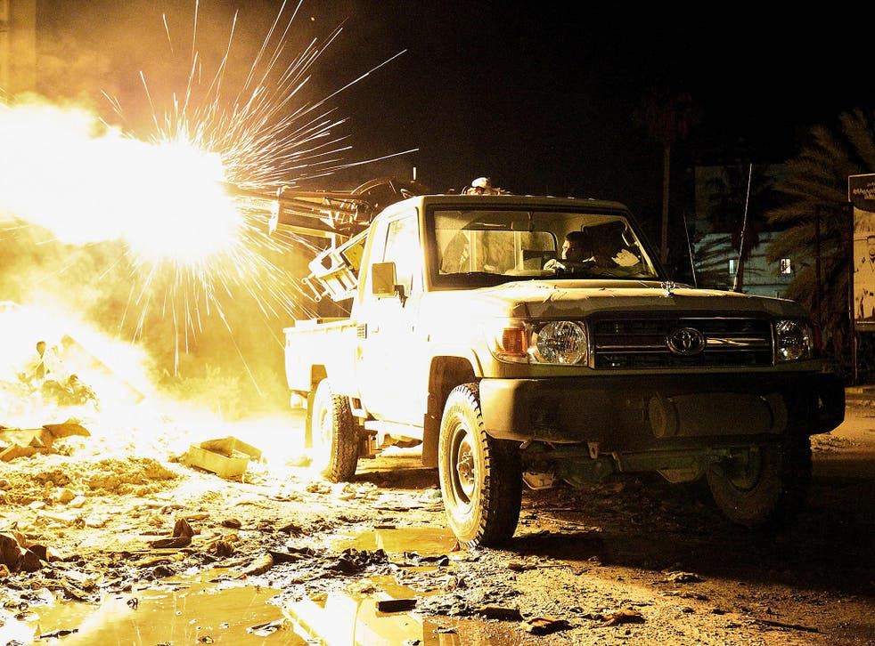 A member of the Libyan National Army (LNA) fires a machine gun mounted on the back of a Toyota pickup truck against jihadists in district of Suq al-Hut in the eastern coastal city of Benghazi