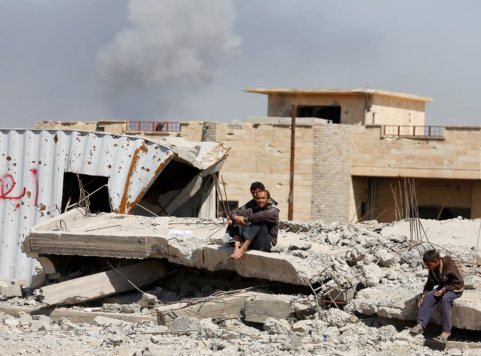 moke rises while displaced Iraqis wait to get food supplies as Iraqi forces battle with Islamic State militants, in western Mosul, Iraq