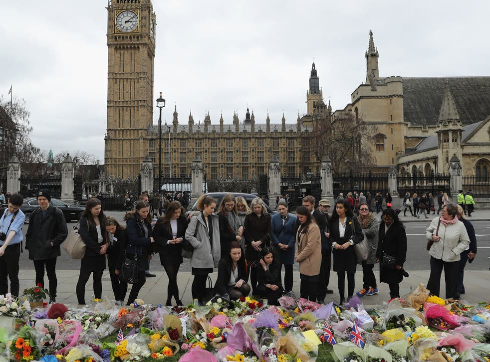 People gather by floral tributes left for the victims of the March 2017 Westminster terrorist attack