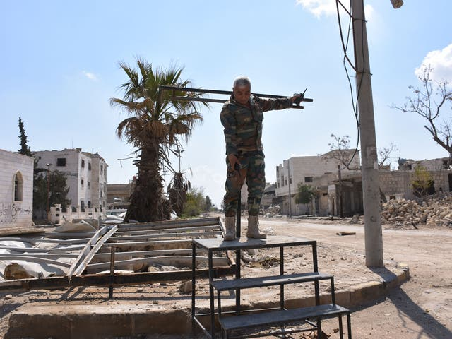 A Syrian soldier demonstrates how the crucifixion stand erected and used by Isis works