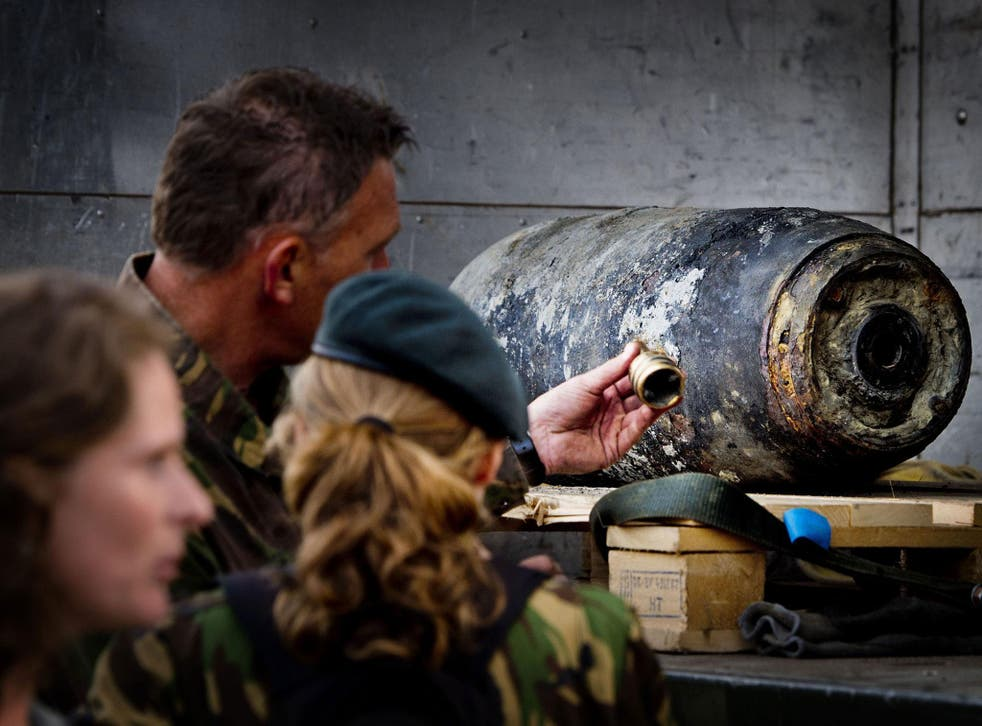 Members of the Dutch Explosive Ordnance Disposal unit stand next to a 500-pound bomb from World War II in Wannenaar, the Netherlands