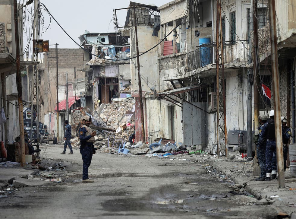 An Iraqi federal police officer stands guard on a Mosul street