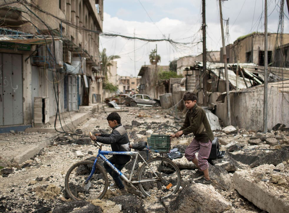 Iraqi boys walk on a destroyed street in a neighborhood recently retaken by Iraqi security forces during fighting against Islamic State militants on the western side of in Mosul