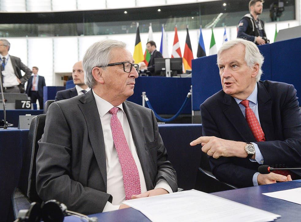 Michel Barnier (R) speaks with European Commission President Jean Claude Juncker at the European Parliament