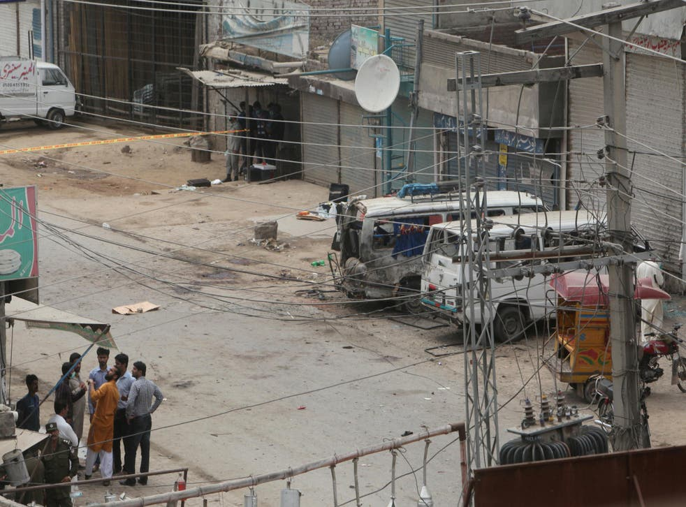 Security officials gather near the site of an explosion, near vehicles taking part in census, in Lahore on April 5 2017