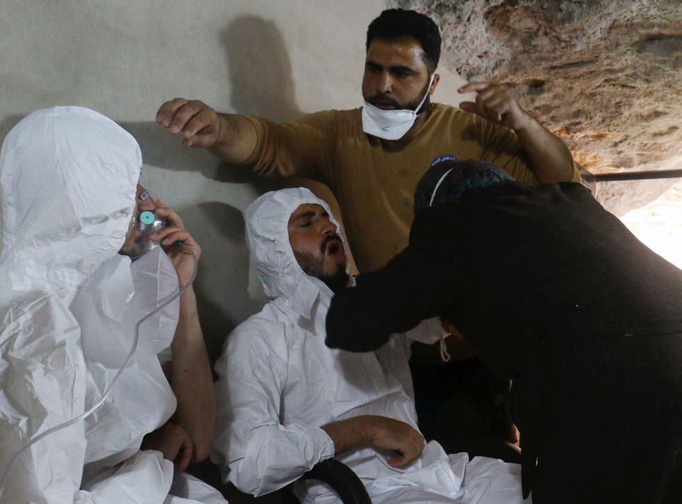 A man breathes through an oxygen mask as another one receives treatment, after what rescue workers described as a suspected gas attack in the town of Khan Sheikhoun on Tuesday