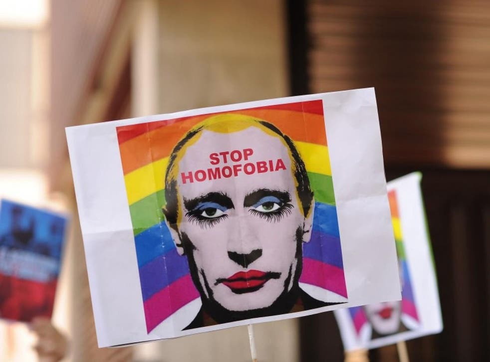 A protester holds up a sign showing Russian President Vladimir Putin wearing lipstick during a protest against Russian anti-gay laws in 2013. A similar image has been declared 'Internet extremism'