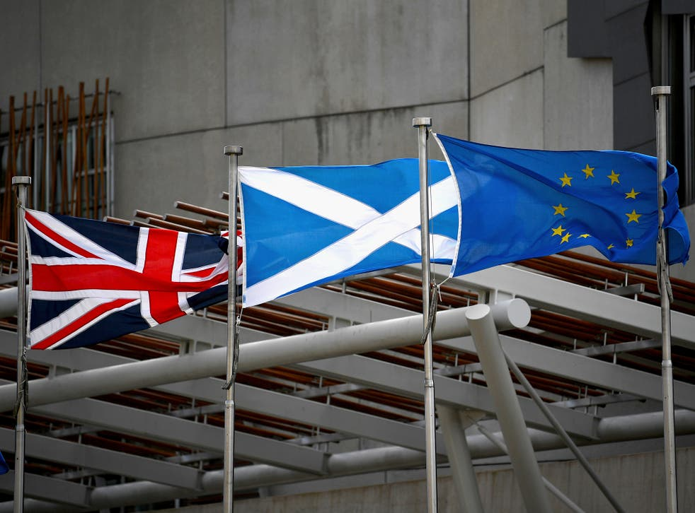 A Saltire, Union Jack and EU flags flutter in the wind outside the Scottish Parliament