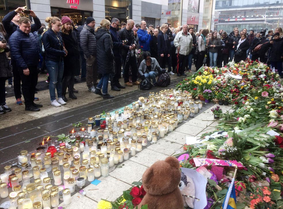 People gather in memorial next to the Ahlens department store following the attack in central Stockholm on Friday