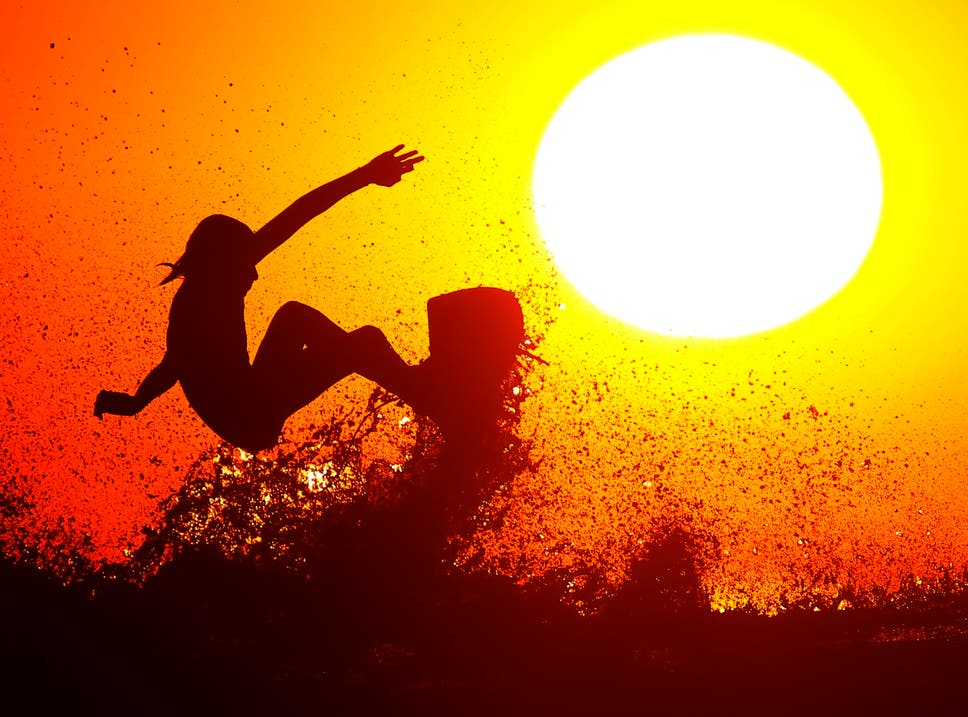 Surfer Cole Clisby rides his surfboard off the top of a wave as the sun sets off the shores of Leucadia, California