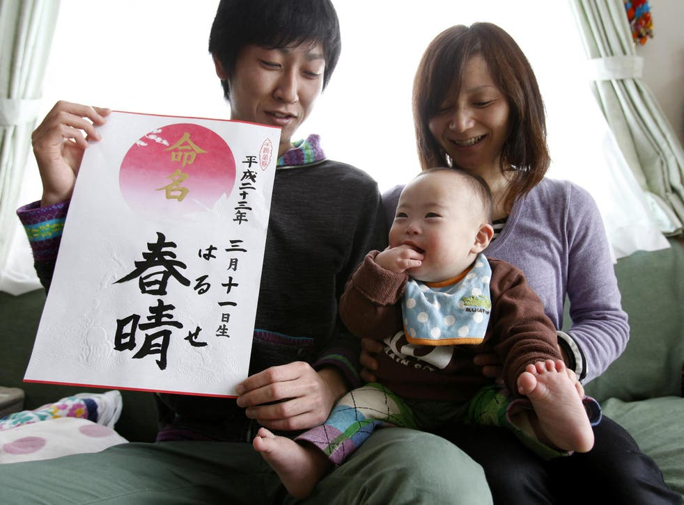 Proud parents Kenji and Hiromi Sato hold their son, Haruse, at their home in Minamisanriku