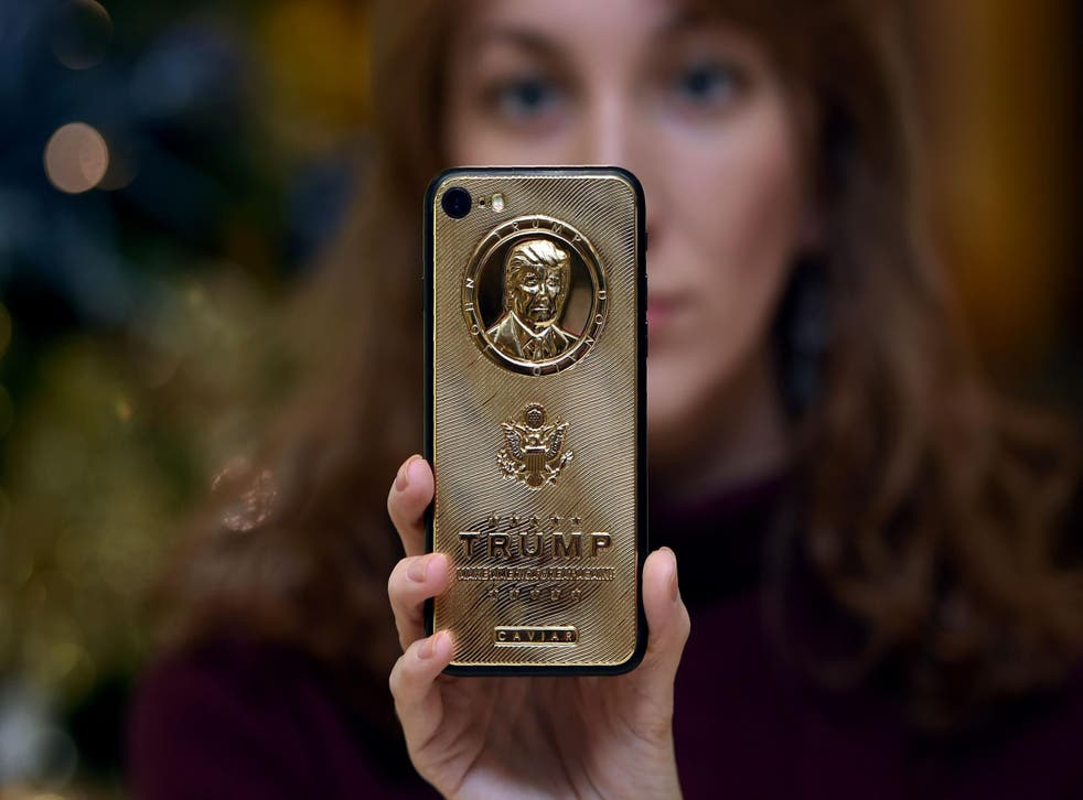 An employee of Caviar Phones displays a gold-plated iPhone case emblazoned with President Donald Trump's image
