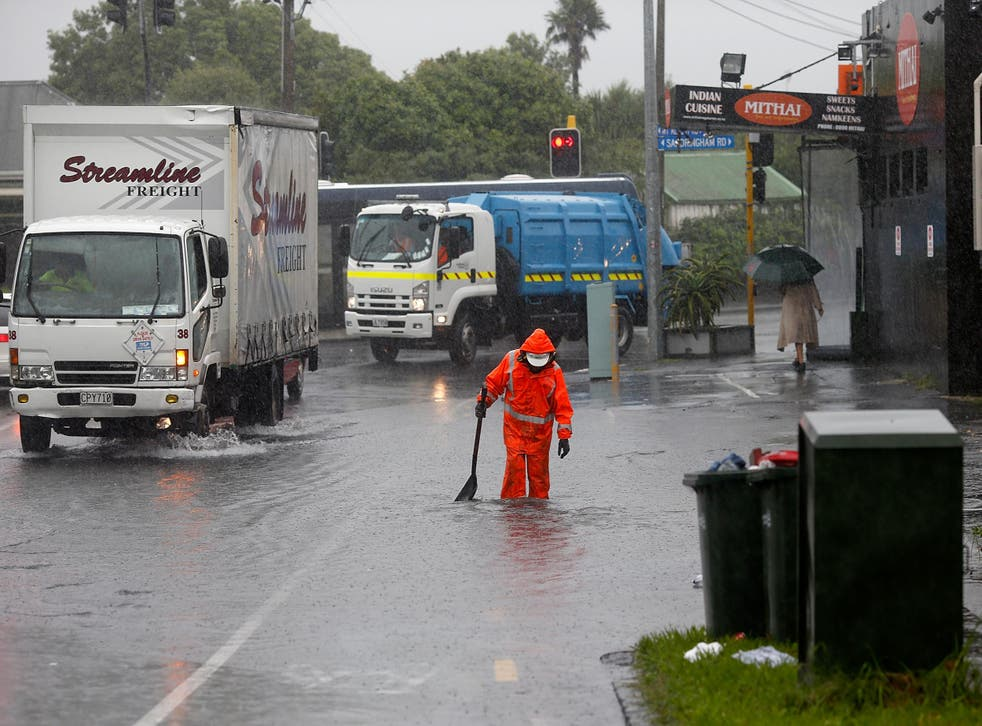 A worker tries to limit the impact of flooding in the New Zealand's largest city, Auckland, as the storm moves down the country