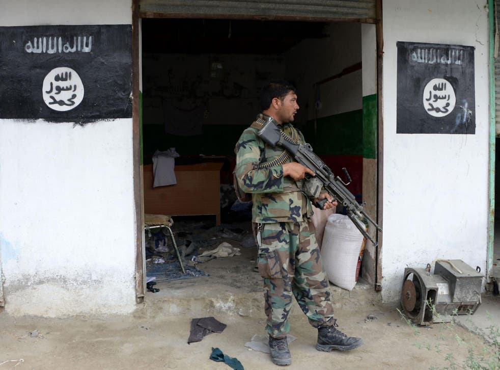 An Afghan government soldier guards a building previously held by Isis in Nangarhar province