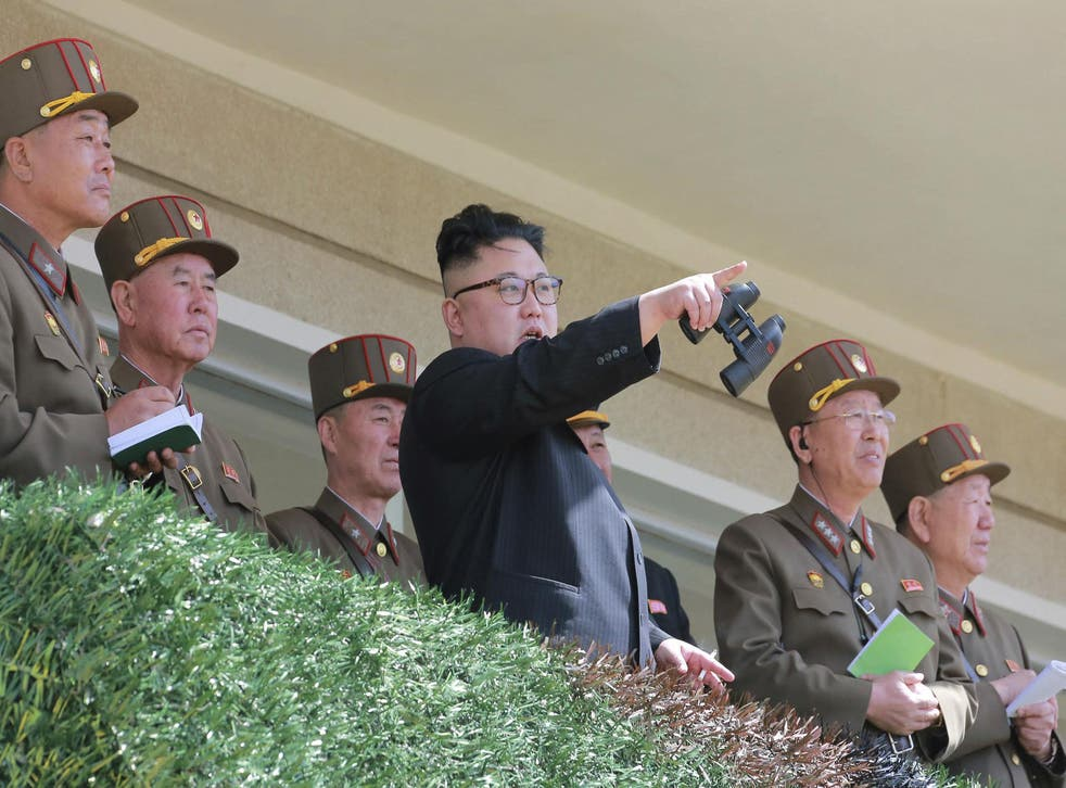 North Korean leader Kim Jong Un watches a military drill at an undisclosed location