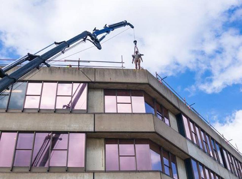 An Antony Gormley sculpture from the series 'Another Place' is lifted onto a roof at UEA