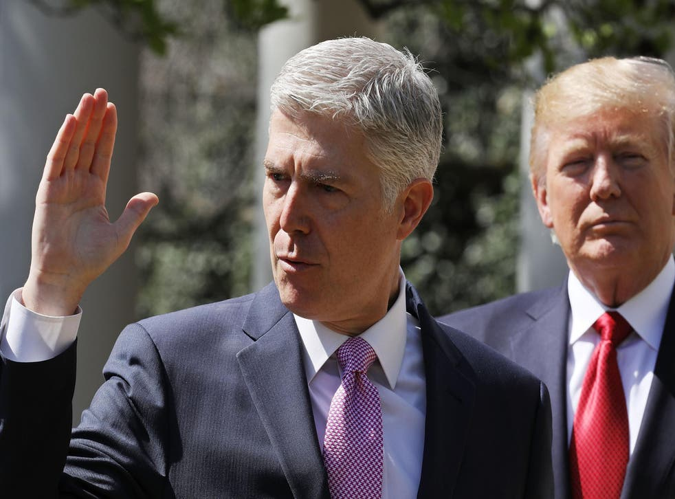 U.S. Supreme Court Associate Justice Judge Neil Gorsuch takes the judicial oath as President Donald Trump looks on