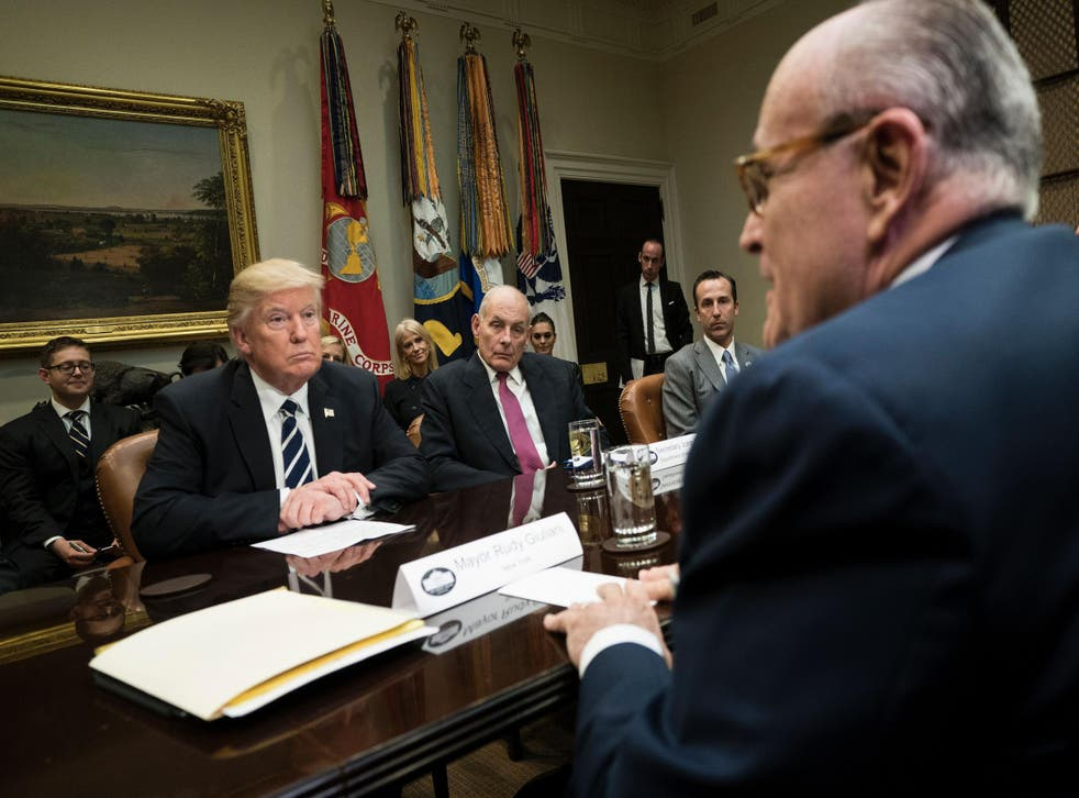 Donald Trump, Secretary of Homeland Security John Kelly, Reed Cordish, Director of Government Initiatives, and others listen while former New York Mayor Rudy Giuliani speaks during a meeting on cyber security