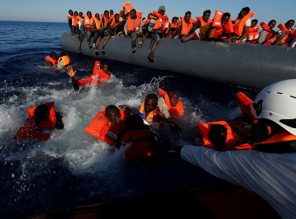 Migrants try to stay afloat after falling off their rubber dinghy during a rescue operation by Moas off the coast of Zawiya in Libya