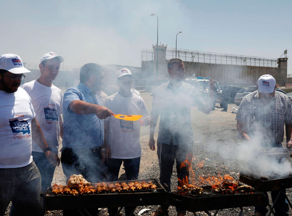 Israeli right-wing activists hold a barbecue outside the Israeli-run Ofer military prison, north of Jerusalem, in the occupied West Bank, where a number of Palestinian prisoners are on a hunger strike