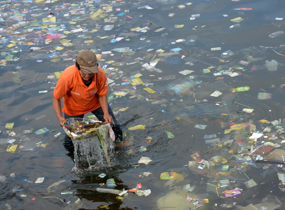 A worker cleaning up Manila Bay in the Philippines. Anywhere in the world, once plastic goes into the water it can be carried to the Arctic by ocean currents