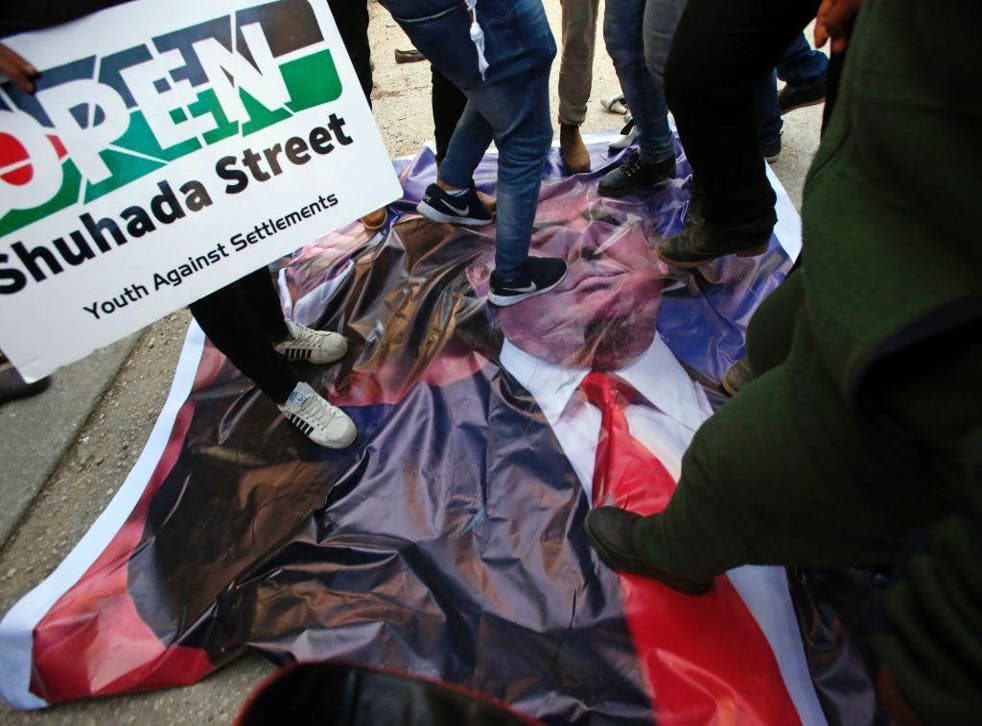 Palestinian demonstrators stand on a poster of US President Donald Trump as they protest against his support of Israel and demand for the Israeli army to re-open Shuhada Street near a Jewish settlement in Hebron on 24 February, 2017