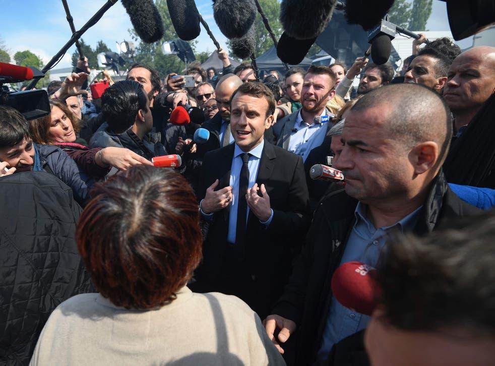 Emmanuel Macron speaks to journalists as he arrives at the Whirlpool factory, in Amiens
