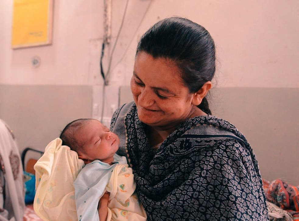 A doctor holds a baby born during the trial of the drug in Pakistan