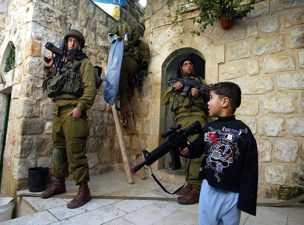 A Palestinian boy plays with his plastic rifle as Israeli soldiers search homes and rooftops in the West Bank town of Hebron in this file photo from 29 December 2006