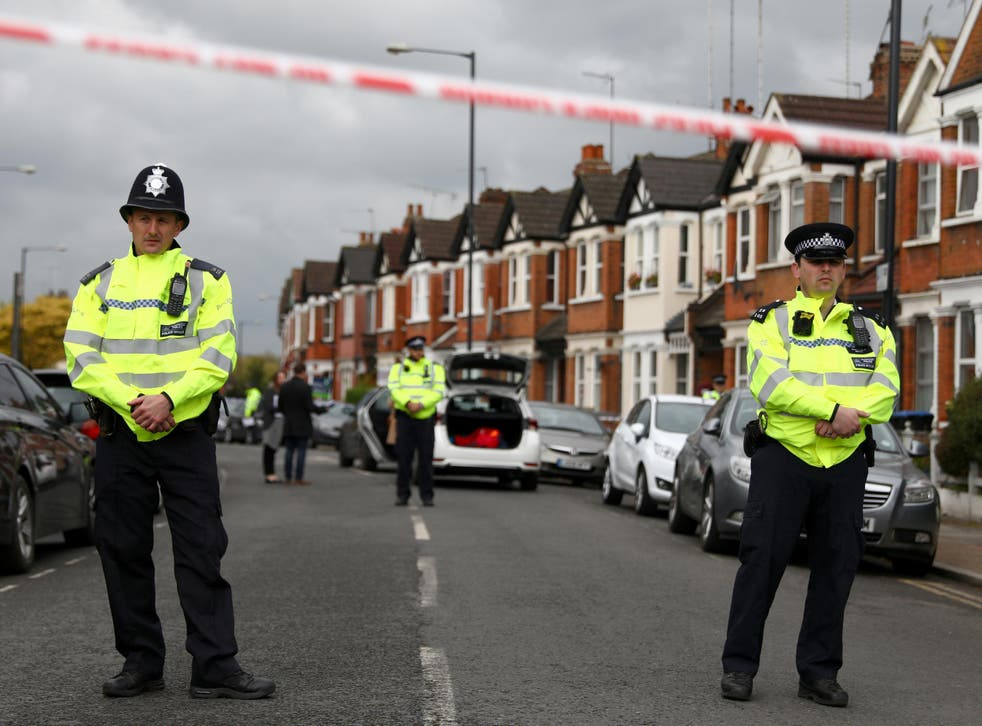 Police officers stand next to terraced housing in Harlesden Road.. British counter-terrorism police said on Friday they had thwarted an active plot after a woman was shot during an armed raid on a house in north London in the second major security operation in the British capital in the space of a few hours