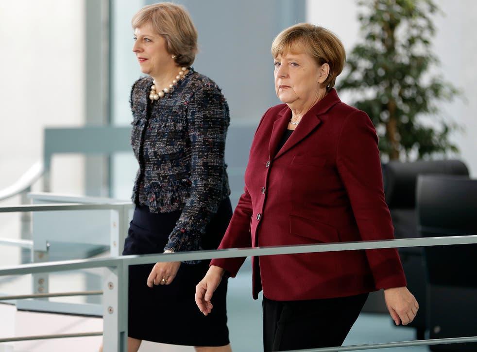 UK prime minister Theresa May walks beside the chancellor of Germany, Angela Merkel