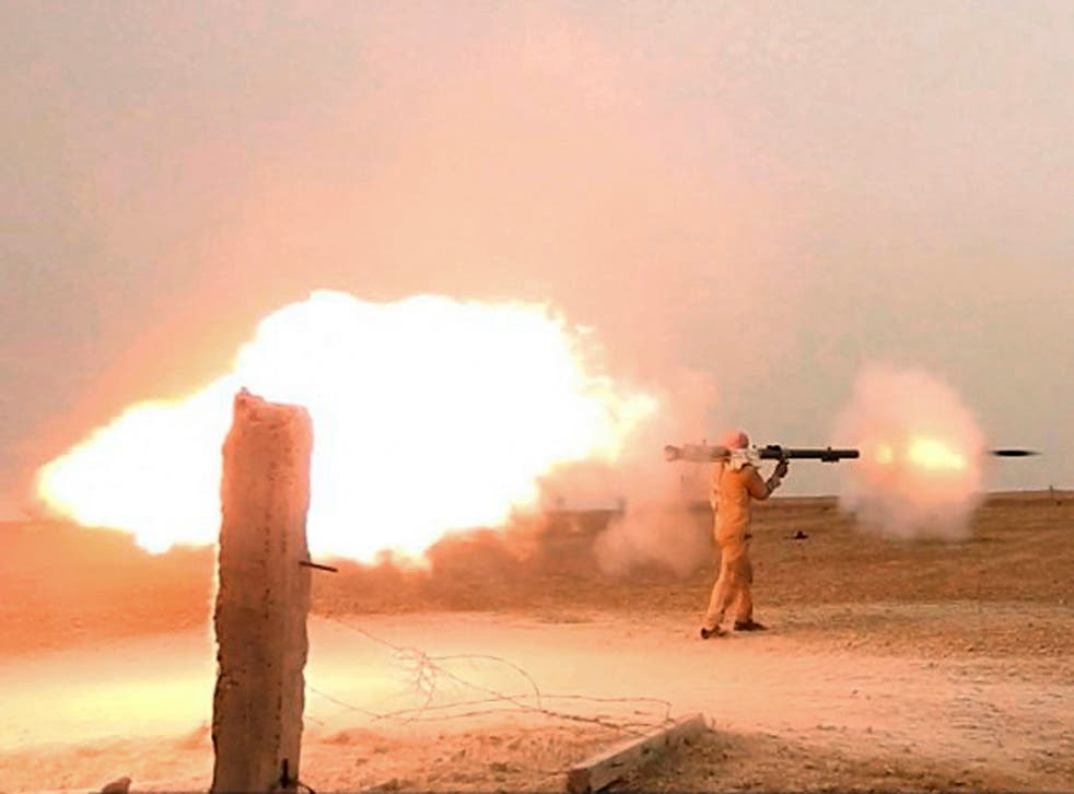 An Islamic State fighter firing his weapon during clashes with  US-backed Kurdish-led Syrian Democratic Forces, in the northern Syrian province of Raqqa