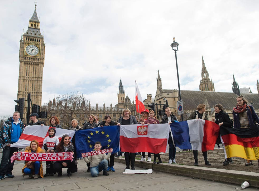 Protesters pose for a photograph with flags from England, European Union, Poland, France and Germany in front of Parliament