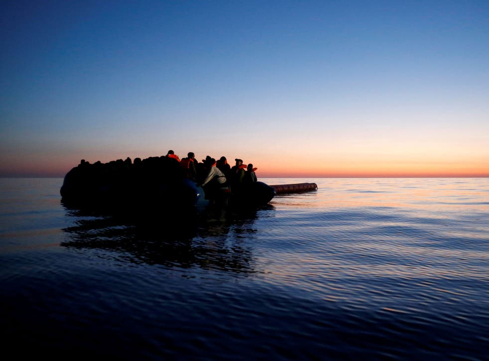 Refugees on a rubber dinghy await rescue at dawn in the central Mediterranean