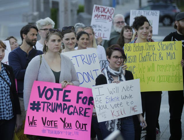 People look on during a healthcare rally in Salt Lake City.