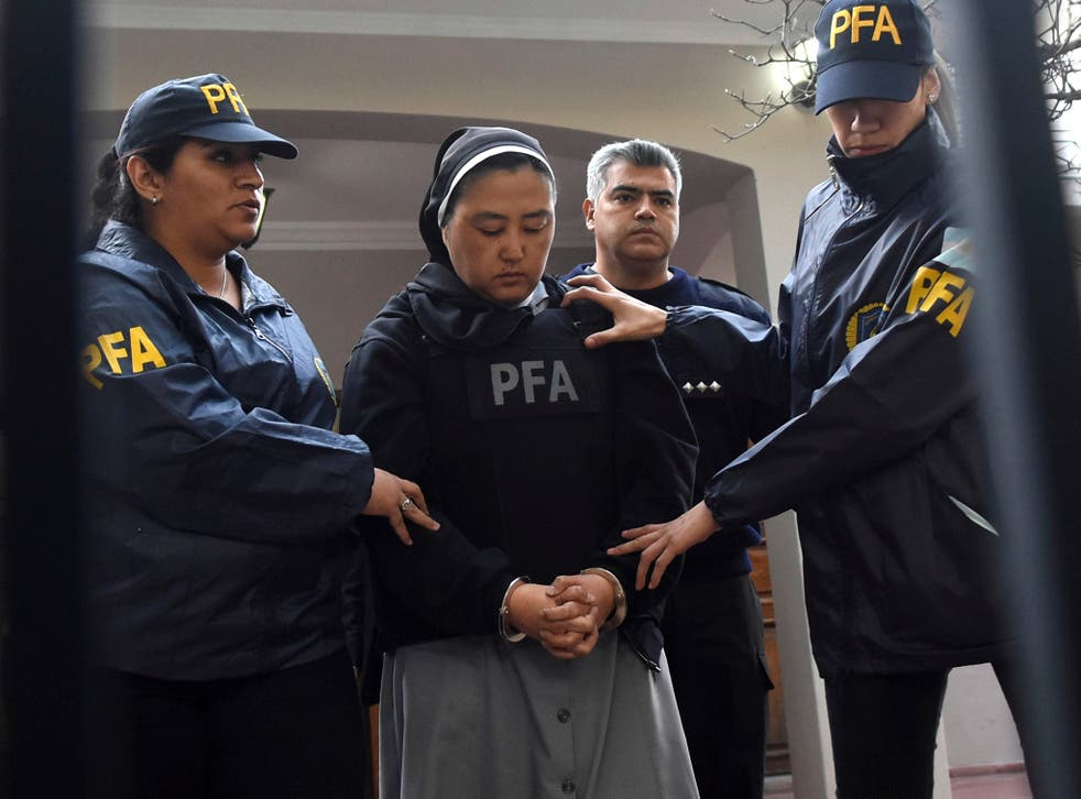 Kosaka Kumiko is escorted out of a police station to attend a court hearing in Mendoza, Argentina