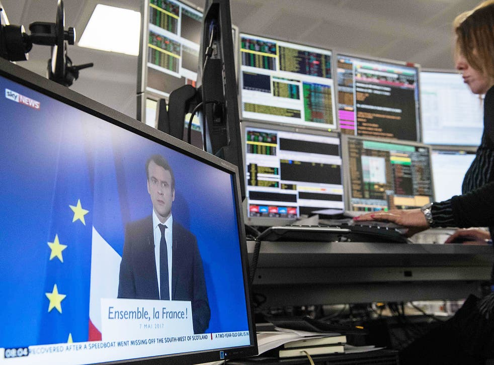 A television screen displays an image of France's President-elect Emmanuel Macron, as traders works on the trading floor of ETX Capital in London